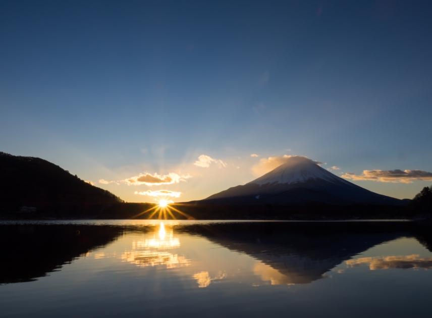 The morning sun rises from ridgeline of Mount Fuji