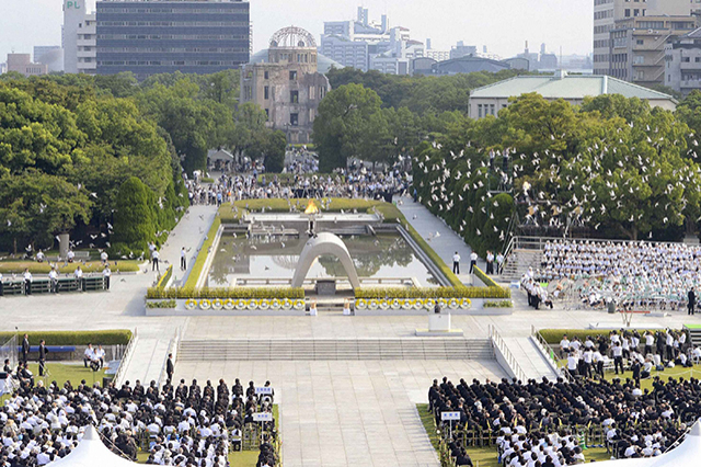 Doves fly over the Peace Memorial Park with a view of the gutted atomic-bomb dome at a ceremony in Hiroshima
